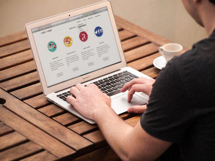 Person sidder udenfor og arbejder på computer