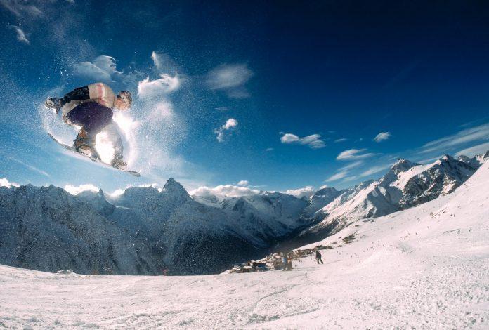 Person står på snowboard ned ad bjerg