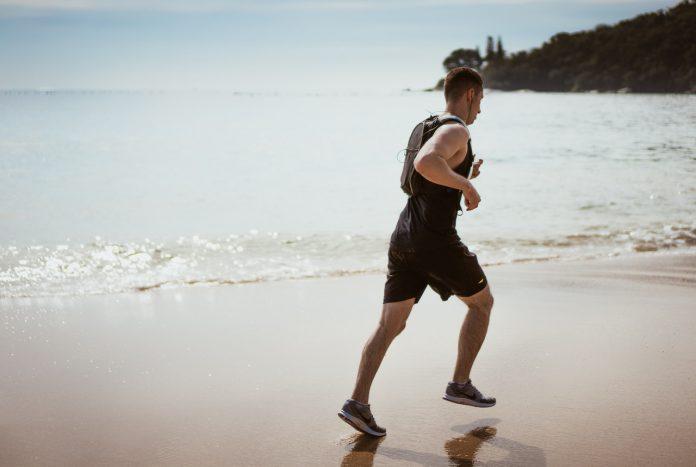 Mand løber på strand